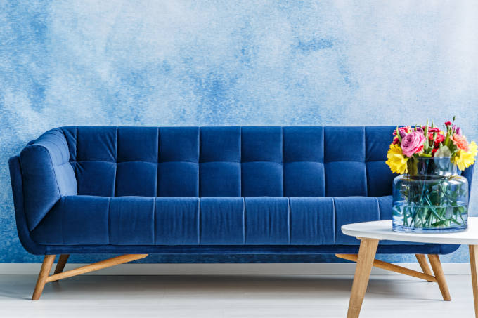 Comfortable navy blue plush sofa and colourful flowers