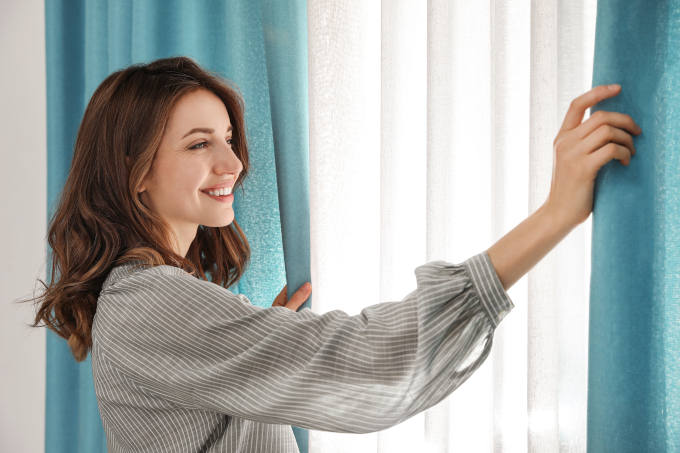 Woman opening window curtains at home